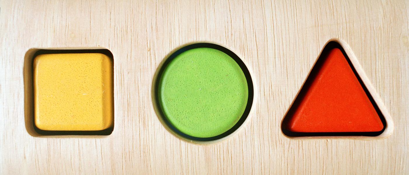 Bild-ID: ets6596. Tre klossar i olika form och färg på ett randigt bord.