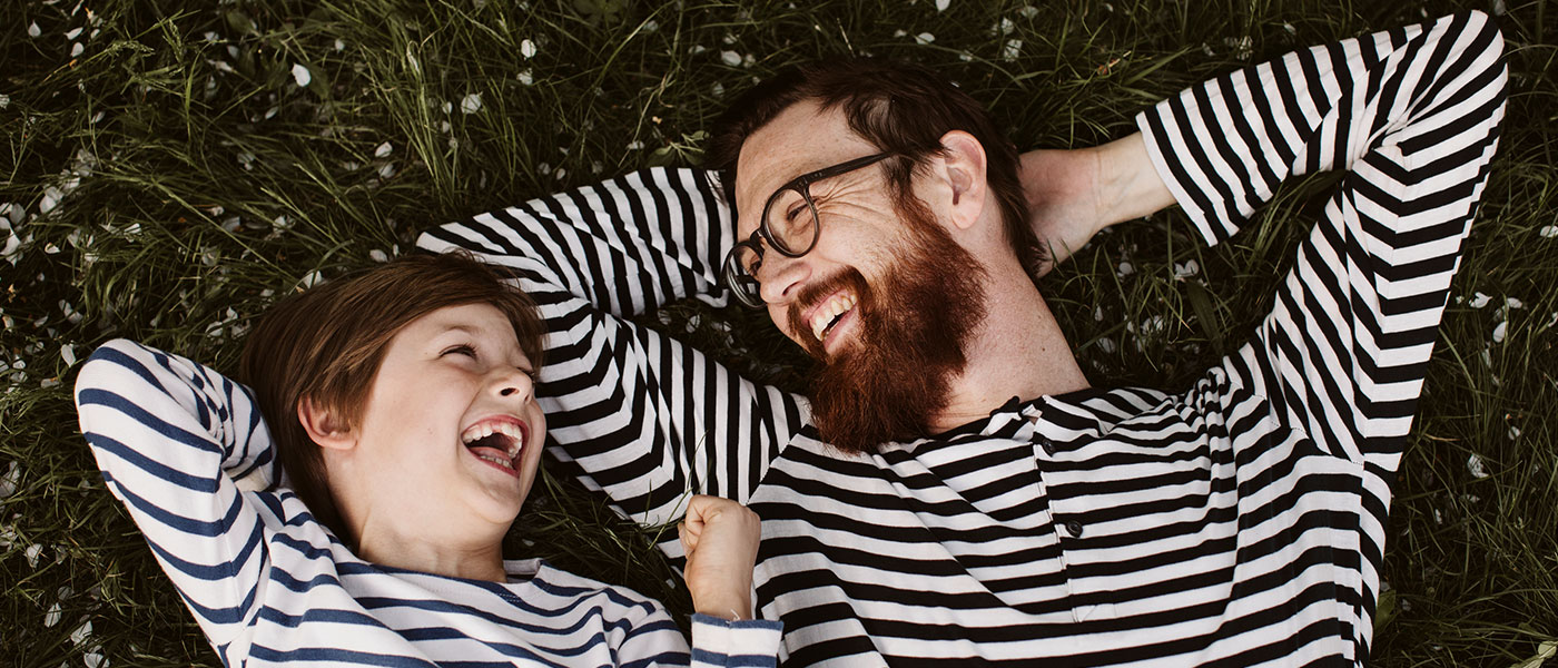 Father and son wearing similar stripped shirts lying on grass. Image-ID: ima183577