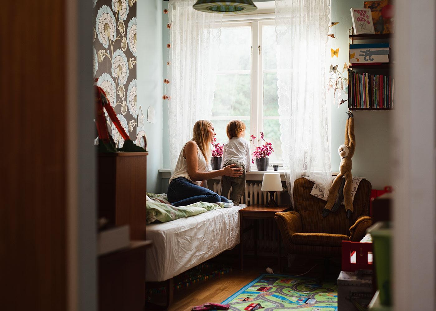 Mamma och son som tittar ut genom fönster. Bild-ID: ima185269