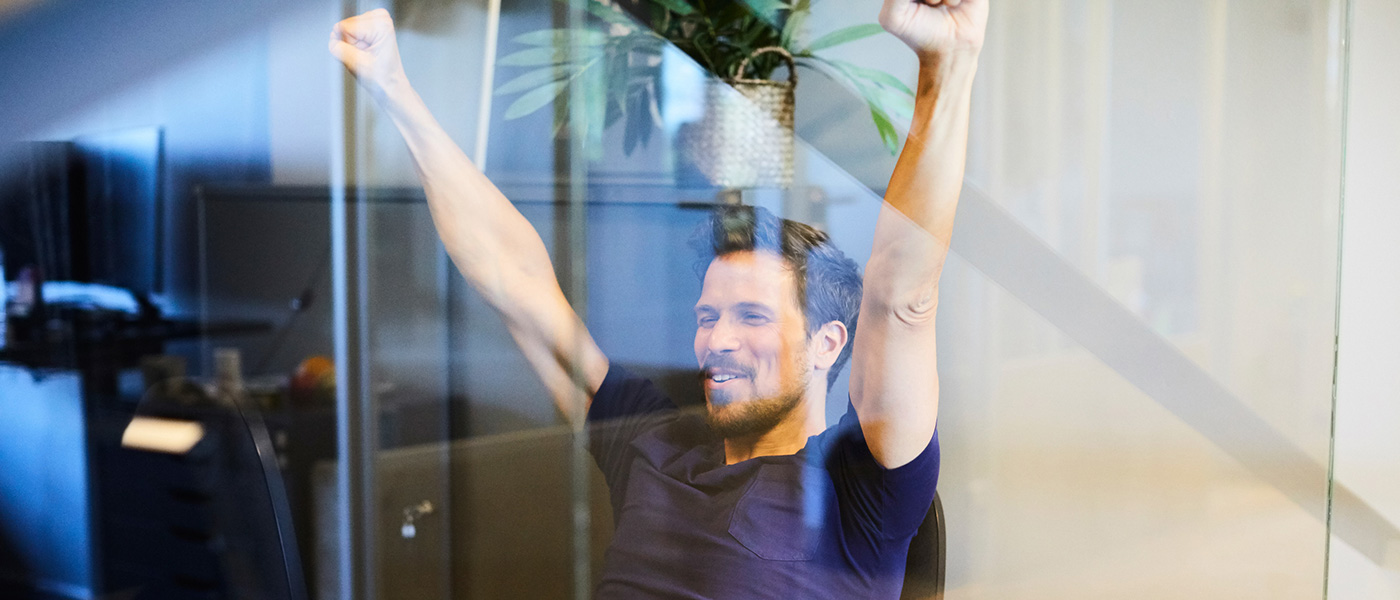 Image ID: masma66225. Creative businessman sitting with arms raised seen through glass in office.