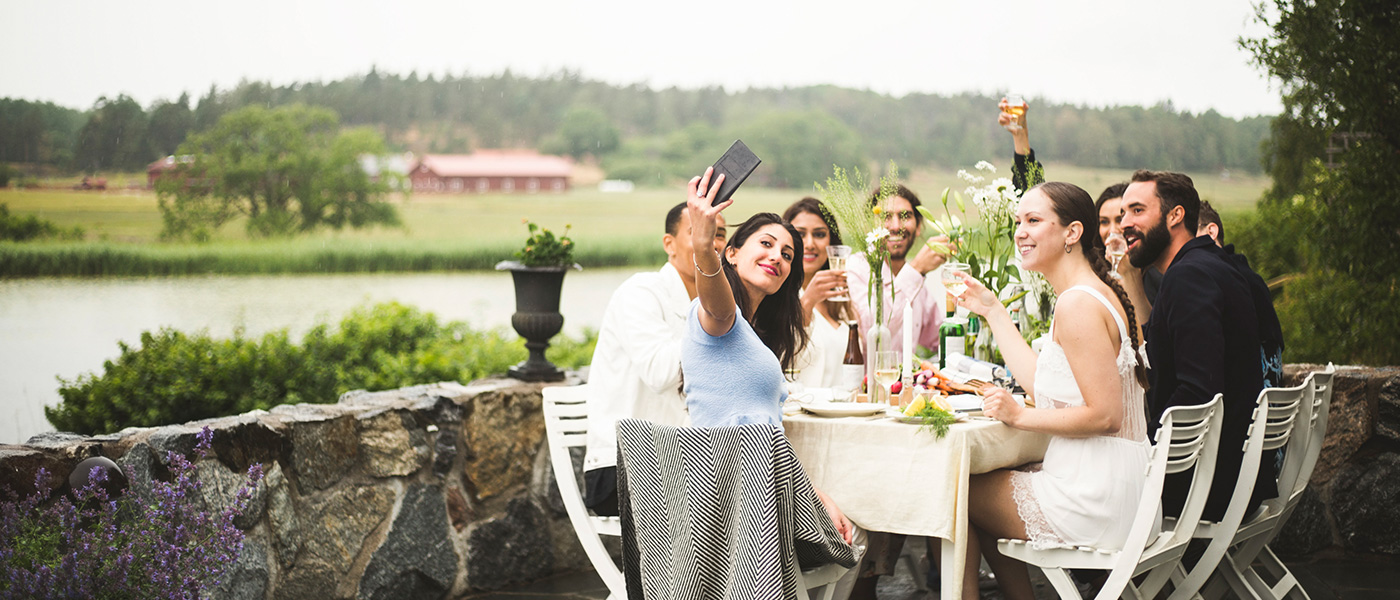 Image ID: masma66924. Smiling woman taking selfie with friends during dinner party in backyard.